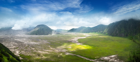 Clouds of thick white smoke emitted by erupting volcano and drifting over ground. Mount Bromo eruption. Tengger Semeru National Park amazing landscape. East Java, Indonesia. Birds eye view