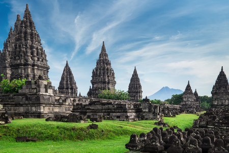 Ancient stone ruins on green field and Candi Prambanan or Rara Jonggrang, Hindu temple compound on background. Impressive architectural site. Yogyakarta, Central Java, Indonesia. Panoramic view. Stock Photo
