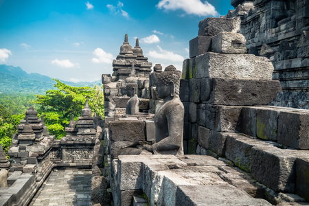 Amazing view of ancient Borobudur Buddhist temple with meditating Buddha statue carved from dark stone against blue sky on background. Great religious architecture. Magelang, Central Java, Indonesia