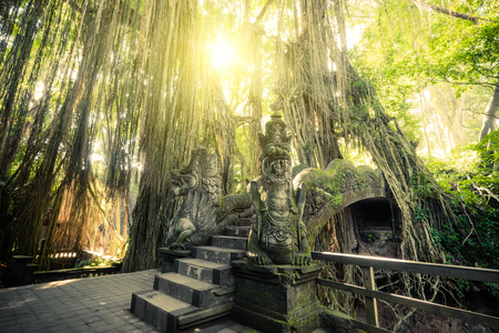 Surreal sunrise colors of fantasy Monkey Forest with Barong Lion bridge and Hindu Temple. Bali, Indonesia. Concept landscape for mysterious background Stock Photo