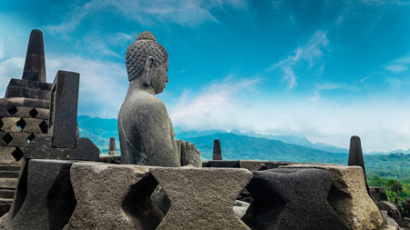 Amazing statue of Buddha sitting in stupa and looking towards gorgeous natural landscape at Candi Borobudur, temple in Magelang, Central Java, Indonesia. Meditation concept Stock Photo