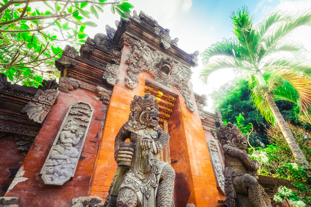 Majestic and tall rock statues Barong Lion Guard near shrine walls lit by sunshine at sunny day, Gunung Kawi Temple Complex, Bali, Indonesia. Stock Photo