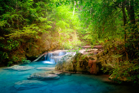 Jungle landscape with flowing turquoise water of Erawan cascade waterfall at deep tropical rain forest. National Park Kanchanaburi, Thailand Archivio Fotografico - 101504143