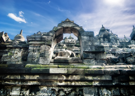 Amazing view of ancient Borobudur Buddhist temple with meditating Buddha statue carved from dark stone against blue sky on background. Great religious architecture. Magelang, Central Java, Indonesia Archivio Fotografico - 102252279