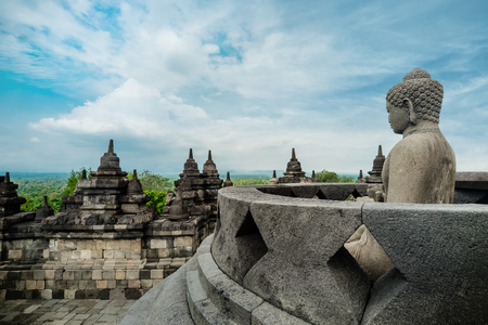 Amazing view of ancient Borobudur Buddhist temple with meditating Buddha statue carved from dark stone against blue sky on background. Great religious architecture. Magelang, Central Java, Indonesia Archivio Fotografico - 101492792