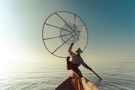 Burmese fisherman on bamboo boat catching fish in traditional way with handmade net. Inle lake, Myanmar (Burma) travel destination Archivio Fotografico - 101481567