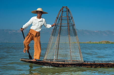 Burmese fisherman on bamboo boat catching fish in traditional way with handmade net. Inle lake, Myanmar (Burma) travel destination Archivio Fotografico - 101497327