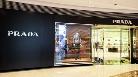 HONG KONG - 23 JAN, 2015: Prada boutique display window with luxury clothes and accessories. Italian luxury fashion house produces shoes, luggage, perfumes, watches.  Ffounded in 1913 by Mario Prada