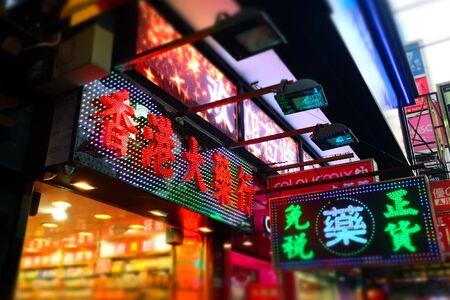 HONG KONG - JAN 15, 2015: Hong Kong cityscape view with plenty bright advertisements and billboards at building facades. Tilt shift lense blur effec Редакционное