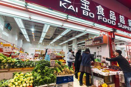 HONG KONG - JAN 15, 2015: People shopping at traditional food supermarket at Hong Kong city street