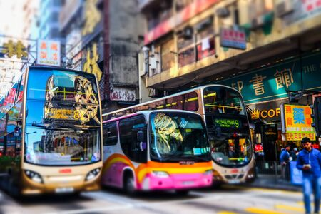 HONG KONG - JAN 15, 2015: Hong Kong cityscape view with city transport and plenty bright advertisements, billboards on skyscrapers facades. Tilt shift lens blur