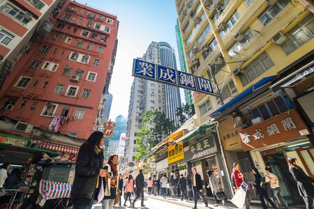 HONG KONG - JAN 15, 2015: Hong Kong cityscape view. People walking at crowded streets with skyscrapers and shopping malls
