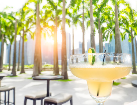 Drinking margarita cocktail in Singapore outdoors cafe. Amazing sunset cityscape  with palm trees and skyscrapers. Luxury vacation in modern asian city Archivio Fotografico - 105525919