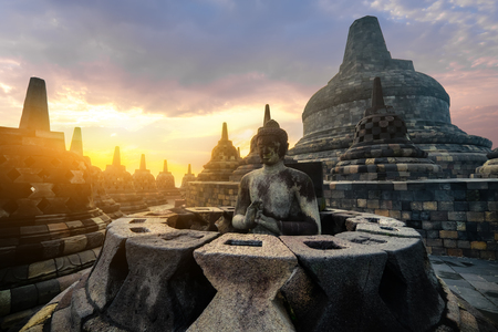 Amazing sunrise view of meditating Buddha statue and stone stupas against shining sun on background. Ancient Borobudur Buddhist temple. Great religious architecture. Magelang, Central Java, Indonesia Archivio Fotografico - 105273982