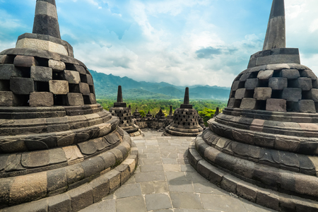 Amazing view of stone stupas at ancient Borobudur Buddhist temple against beautiful landscape on background. Great religious architecture. Magelang, Central Java, Indonesia Archivio Fotografico - 105273986