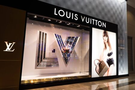HONG KONG - 22 JAN, 2015: Louis Vuitton boutique display window with mannequin in luxury clothes and accessories for exclusive shopping. French fashion house founded in 1854 by Louis Vuitton Редакционное