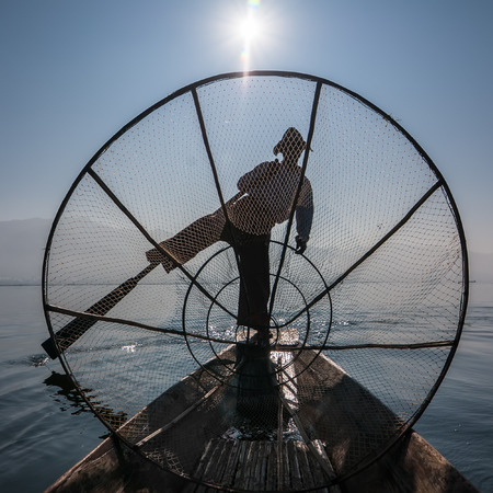 Burmese fisherman on bamboo boat catching fish in traditional way with handmade net. Inle lake, Myanmar (Burma) travel  destination Archivio Fotografico - 115909410