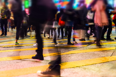 Blurred image of people moving in crowded night city street.. Hong Kong Archivio Fotografico - 115909417