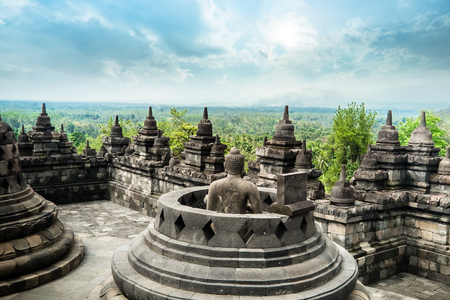 Amazing view of ancient Borobudur Buddhist temple with meditating Buddha statue carved from dark stone against blue sky on background. Great religious architecture. Magelang, Central Java, Indonesia Archivio Fotografico - 117040157