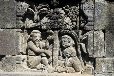 Closeup wall ornamented with bas-reliefs religion scene. Highly detailed stone carving. Borobudur Buddhist temple, Magelang, Indonesia Archivio Fotografico - 117040170