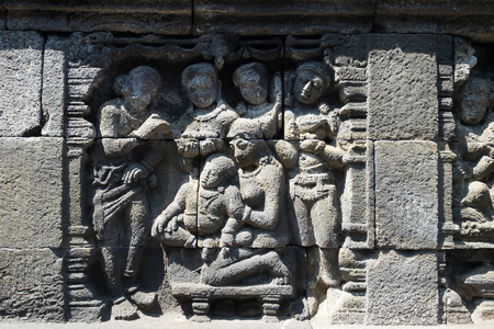 Closeup wall ornamented with bas-reliefs religion scene. Highly detailed stone carving. Borobudur Buddhist temple, Magelang, Indonesia Archivio Fotografico - 117040175