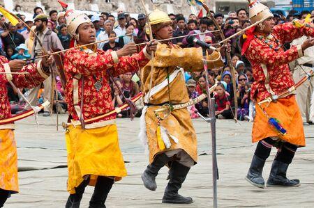 LEH, INDIA - SEPTEMBER 08, 2012: Man in traditional Tibetan clothes performing folk dance.  Annual Festival of Ladakh Heritage in Leh, India. September 08, 2012 Редакционное