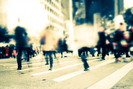 Blurred image of pedestrians people moving on zebra crosswalk at crowded city.  Tilt shift, abstract urban background. Hong Kong