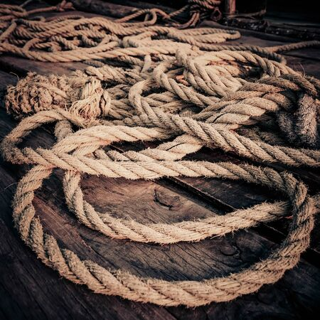 Coarse coconut rope at wooden fishing boat deck under sunset sunlight. Detail of chinese fishing nets at Cochin (Kochi). South India, Kerala, Kochin. High contrast, grunge processing image