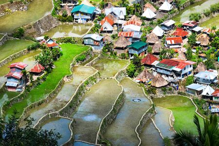 Village houses near rice terraces fields. Amazing abstract texture with sky colorful reflection in water. Ifugao province. Banaue, Philippines 版權商用圖片