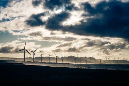 Wind turbine power generators silhouettes at ocean coastline at sunset. Alternative renewable energy production in Philippines 版權商用圖片