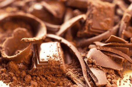 Chocolate background. Bars and strips of chocolate with cocoa powder. Shallow depth of field 版權商用圖片