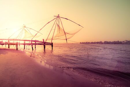 Amazing sunset colors of tropical beach. Ocean coast landscape with chinese fishing nets silhouette at Cochin (Kochi). South India, Kerala, Kochin