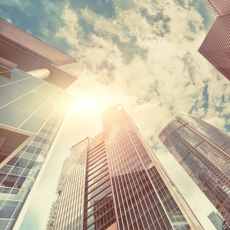 Abstract futuristic cityscape view with modern skyscrapers. Sun shines in sunset sky reflecting in windows. Urban architecture background 版權商用圖片