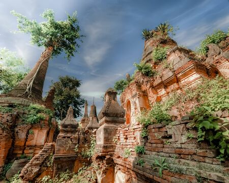 Ruins of ancient stupas of Shwe Indein Pagoda over blue sky. Indein village, Inle Lake, Shan State, Myanmar (Burma) Фото со стока