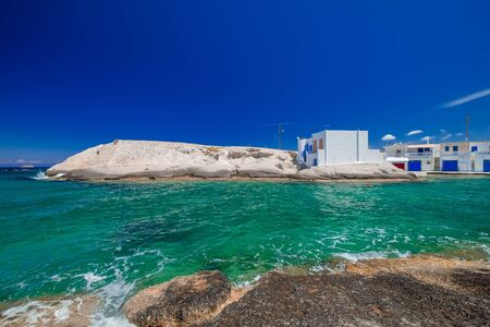 View of traditional fishing village with white houses on coastline. Turquoise water of Aegean sea Milos island. Amazing mediterranean landscape. Greece