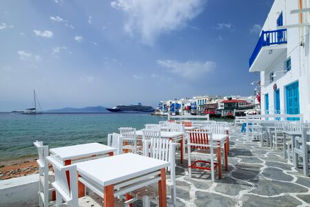 Outdoor restaurant with sea view near romantic colorful Little Venice at sunny day. Yachts on Aegean sea. Amazing touristic place, People walking along promenade, Alefkandra area. Greece vacation