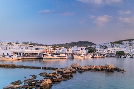 Panoramic view of sunset at popular tourist attraction in Paros island, Naousa town. Promenade zone with bars and restaurants along harbor. Aegean Sea and boats in quay. Amazing evening in Greece