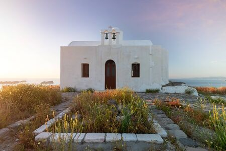 Sunset at Plaka, chief town of Milos island on Kastro hill. Top view in beautiful evening, Greece. Old fortress and ancient church. Peaceful water of sea and mountains on background
