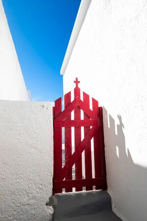 Red door of entrance to Greek Orthodox church. Cross as christianity religion symbol under blue sky. Abstract minimal style architecture and religious concept. Traditional mediterranean colors. Greece