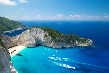 Picturesque top view of Navagio Beach or Shipwreck Beach. Old ship after crash on sand in lagoon surrounded by high rocks. Boats floating turquoise Ionian Sea. Paradise in Zakynthos island, Greece Stock Photo