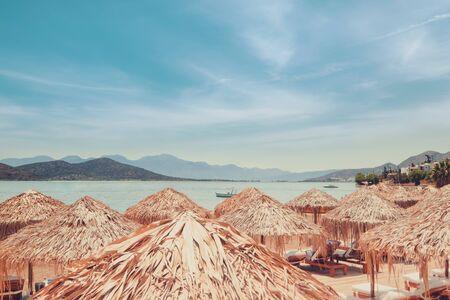 Abstract view of amazing beach landscape with straw umbrella near azure Aegean sea. Zdjęcie Seryjne