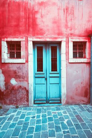 Old scratched blue door and small windows at colorful red house wall, Abstract view of city street with abandoned building. Shabby texture and grunge urban background. Greece Zdjęcie Seryjne