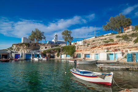 Mandrakia traditional fishing village with syrmata. Orthodox church and boat garages on Aegean sea, Milos island. Mediterranean plants and greek architecture. Greece paradise vacation