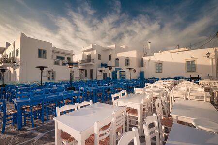 Cafe and restaurants at amazing narrow street of popular destination on Paros island. Greece. Traditional architecture and colors of mediterranean city at sunrise. Calm morning at romantic destination Zdjęcie Seryjne