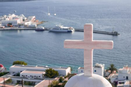 Panorama of sunset above Mykonos town harbor with Greek Orthodox church cross in front. Old windmills (Kato Mili)- famous landmark and tourist attraction on background. Ships on Aegean sea, Cyclades