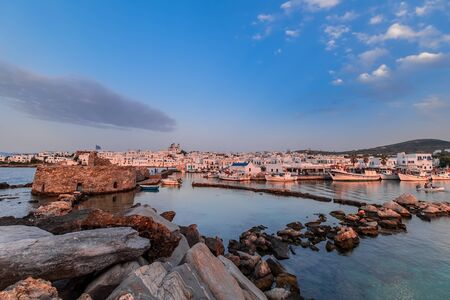 Naousa town - main tourist attraction in Paros island, Cyclades. Harbor with ancient stone Venetian Castle for surveilling the Aegean Sea. Beautiful sunset in old port with boats. Greece paradise