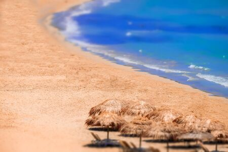 Tilt shift lens blur. Abstract view of amazing beach landscape with straw umbrella near azure sea. Mediterranean paradise in Greece. Travel background and destinations Zdjęcie Seryjne