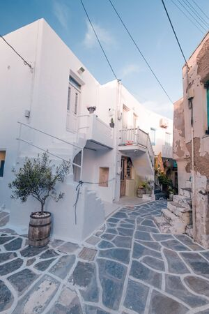 Amazing narrow streets of popular destination on Paros island. Greece. Traditional architecture and colors of mediterranean city. Blue doors, white buildings and bougainvillea flowers in paradise
