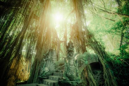 Surreal sunrise colors of fantasy Monkey Forest with Barong Lion bridge and Hindu Temple. Bali, Indonesia. Concept landscape for mysterious background Zdjęcie Seryjne