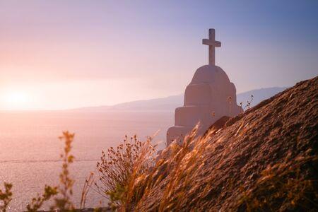 Amazing sunset colors of Aegean sea. Orthodox church cross, christianity religion symbol. Mykonos island. Greece